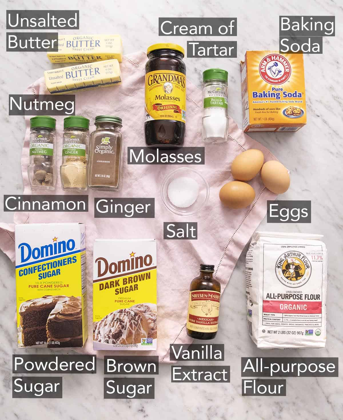 Ingredients to make gingerbread cookies with text labels on a marble counter.