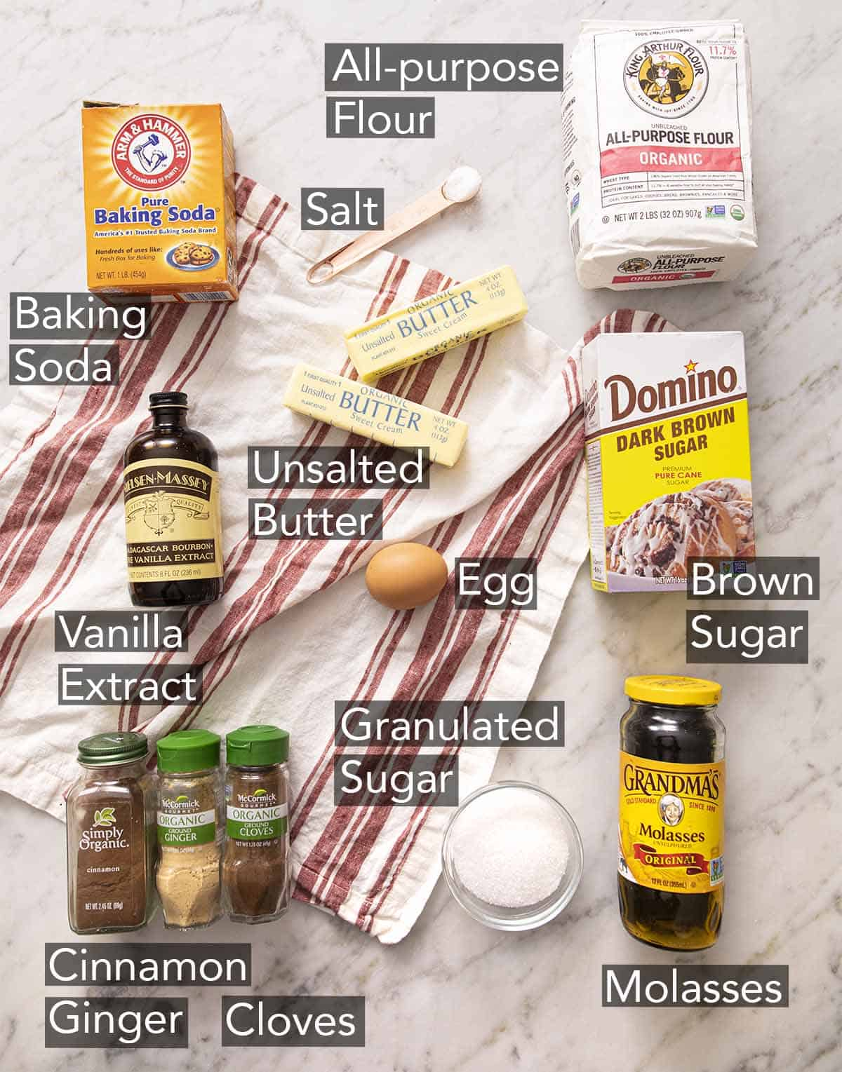 Ingredients to make gingersnaps laying on a striped napkin