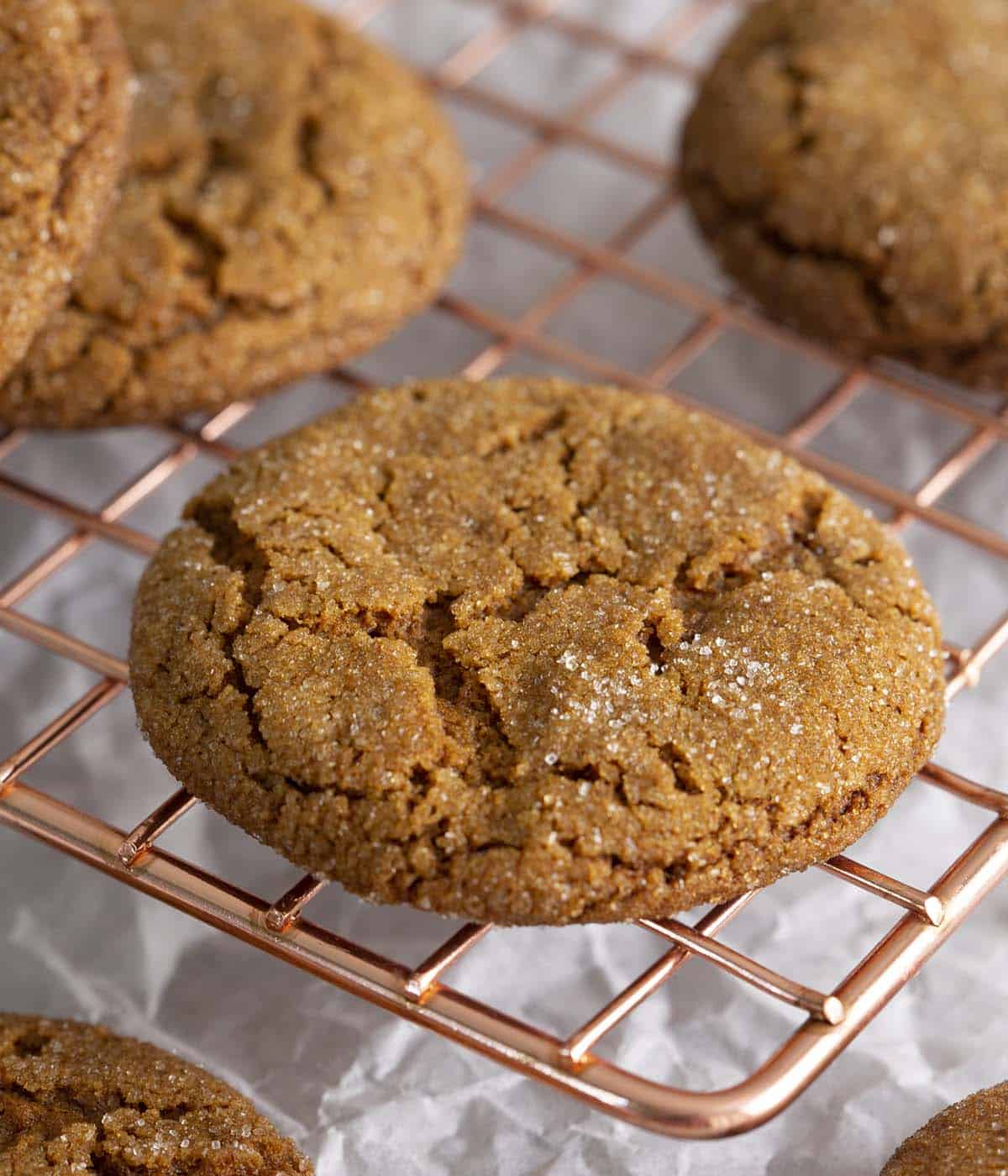 Molasses cookies on a copper cooling rack.