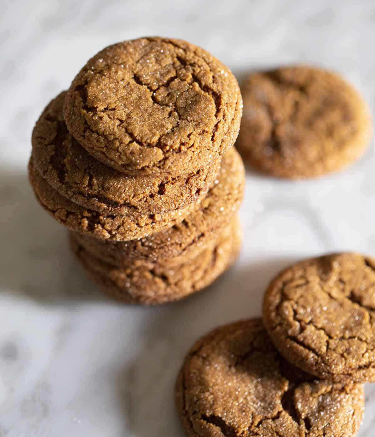 Molasses cookies stacked on a marble table.