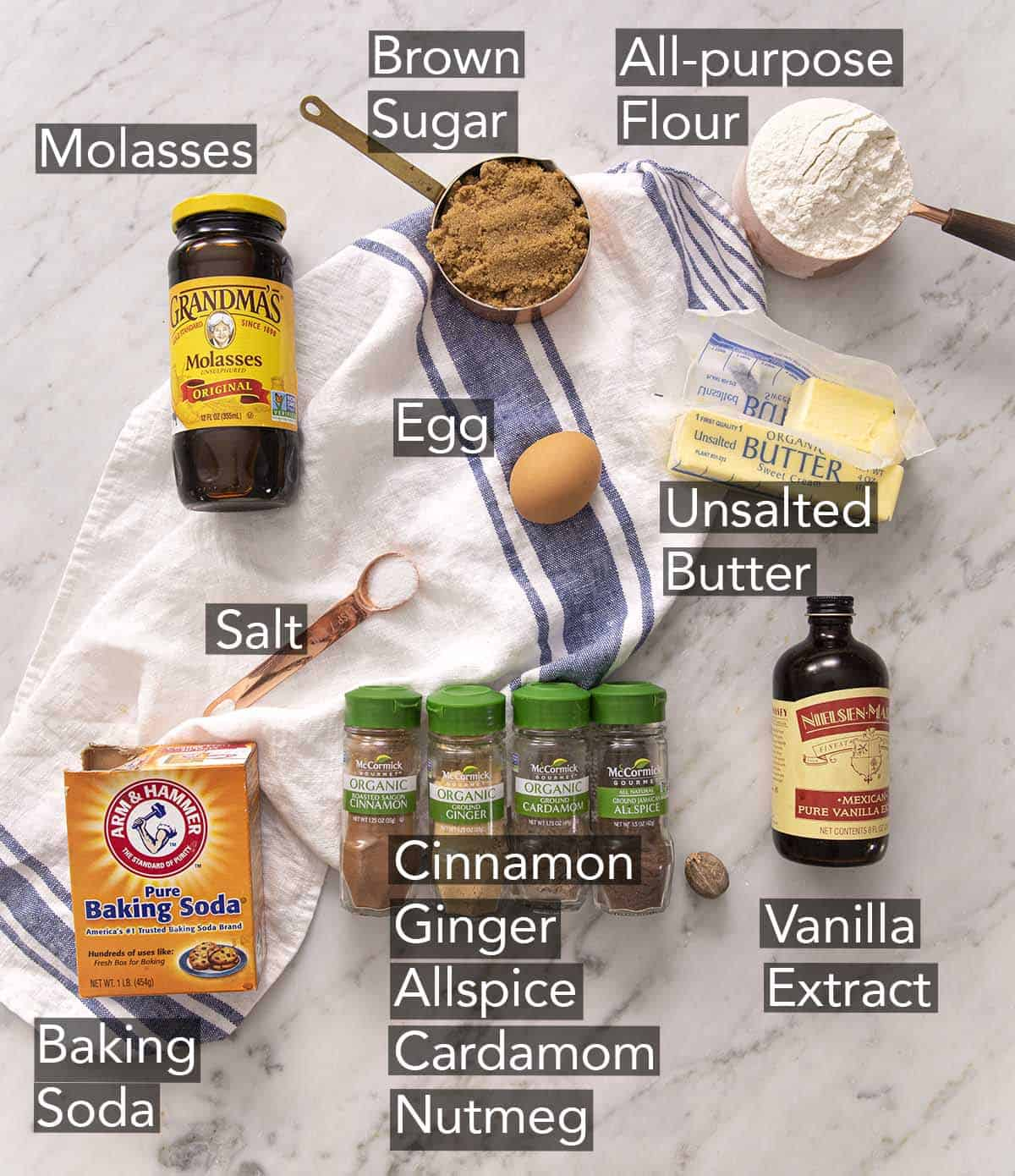 Ingredients to make molasses cookies on a marble counter.