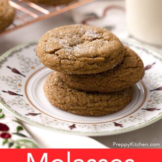 Three molasses cookies on a holiday plate next to a glass of milk.
