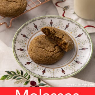 A broken and whole molasses cookie on a Christmas plate.