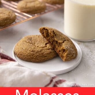 A broken and whole molasses cookie on a white plate.
