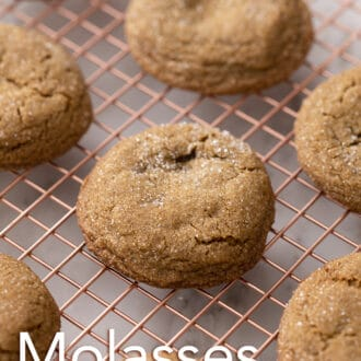 A group of molasses cookies on a cooling rack.