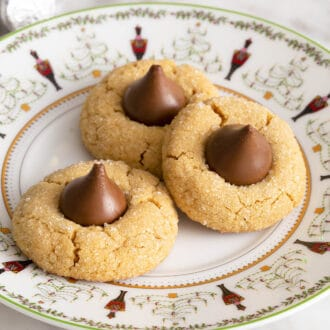 3 peanut butter blossom cookies on a christmas plate
