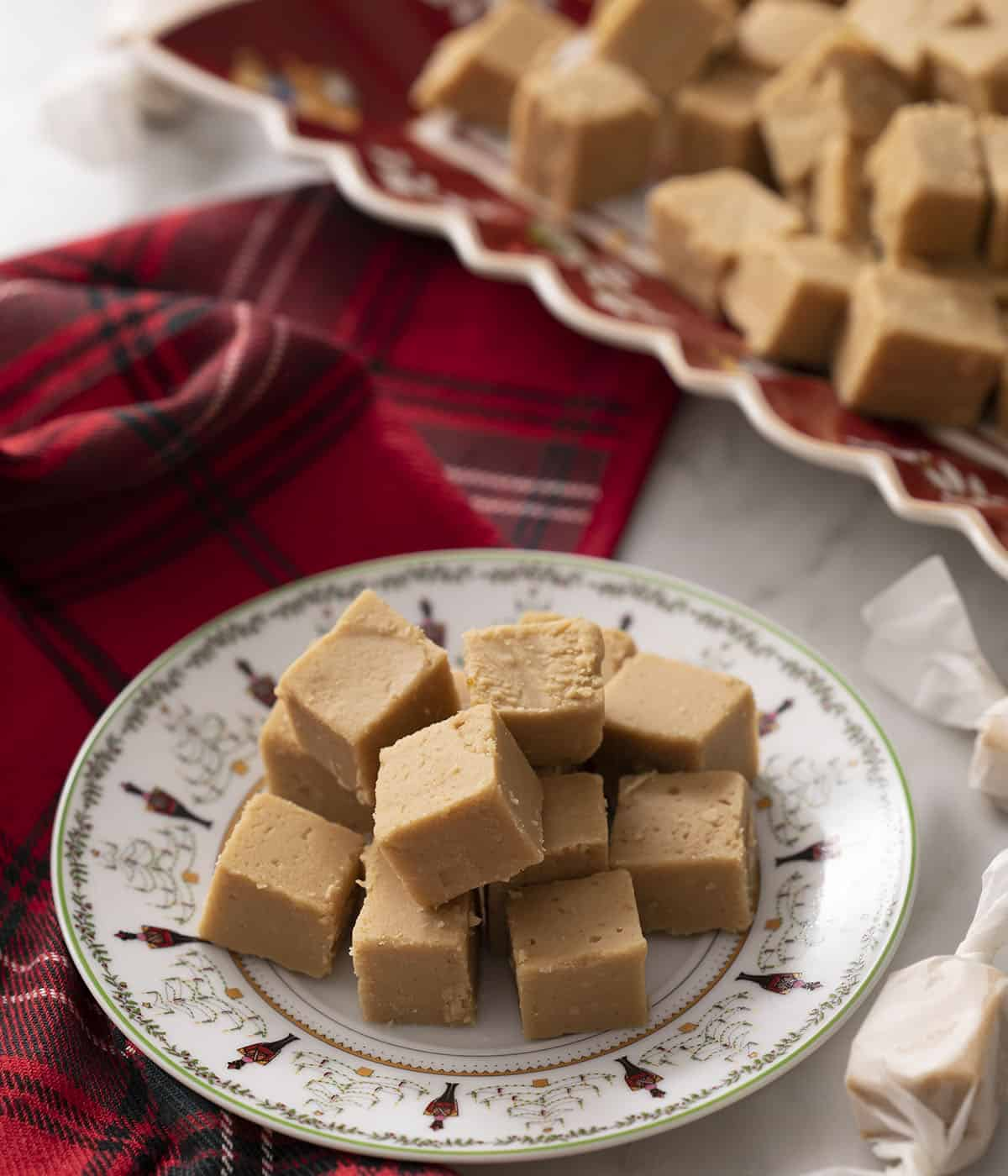 A pile of peanut butter fudge on a holiday plate.