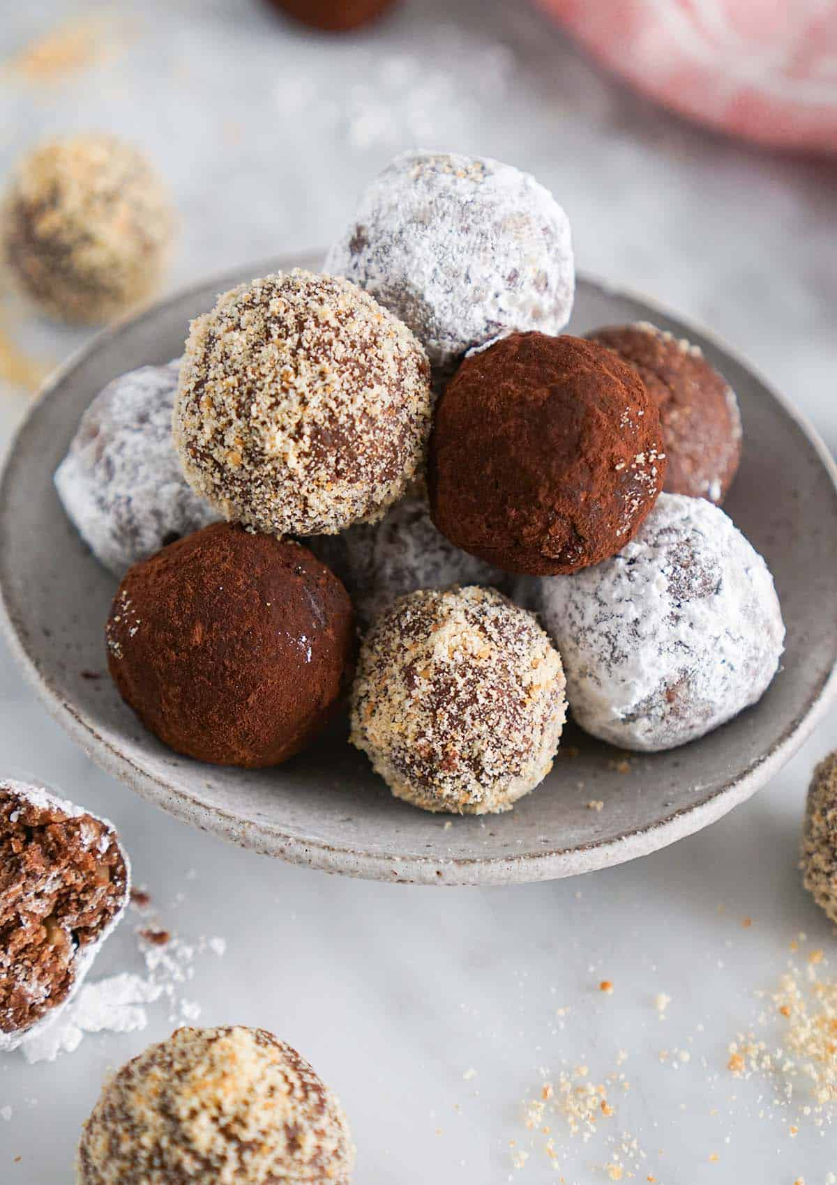 A pile of rum balls with different coverings on a marble surface.