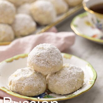 3 russian tea cakes sitting on a plate with a pink napkin