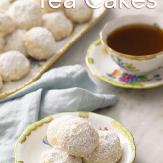 russian tea cakes on a white and green plate with a cup of tea