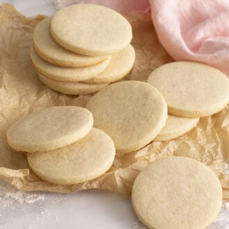 A group of round sugar cookies on a marble table.
