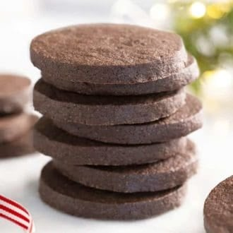 A stack of round chocolate sugar cookies on a marble table.