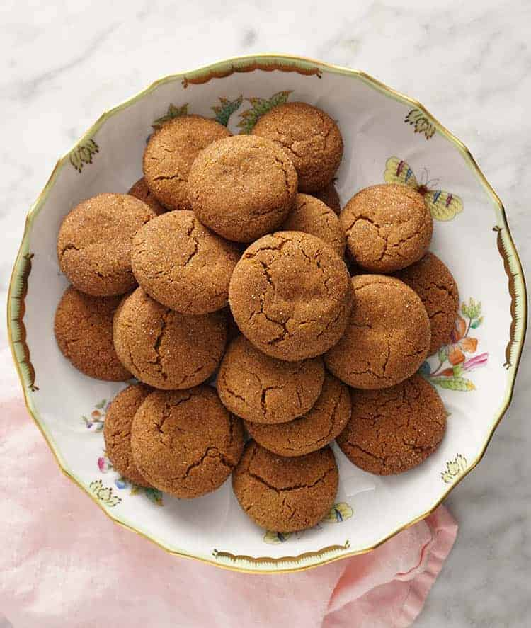 a porcelain bowl filled with ginger snap cookies.