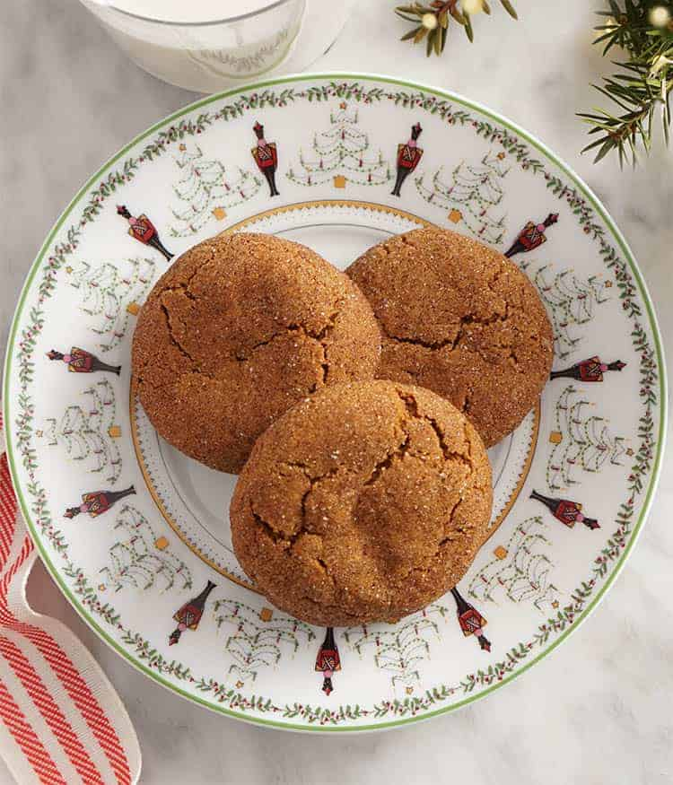 Ginger snap cookies on a holiday plate nest to a glass of milk and a red ribbon.
