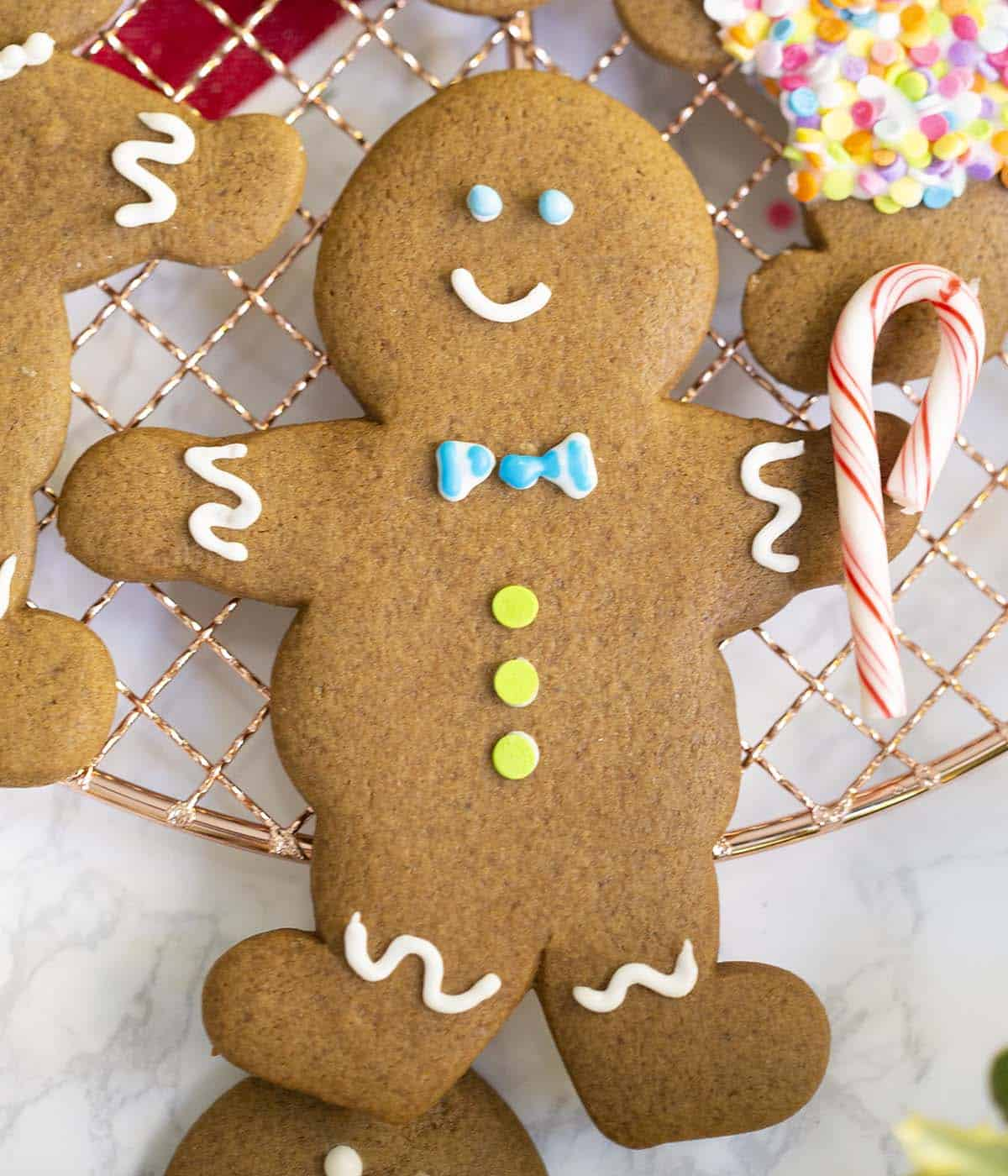 Two photos showing royal icing for gingerbread men being mixed then piped onto gingerbread cookies.