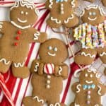A group of decorated gingerbread cookies on a striped linen.