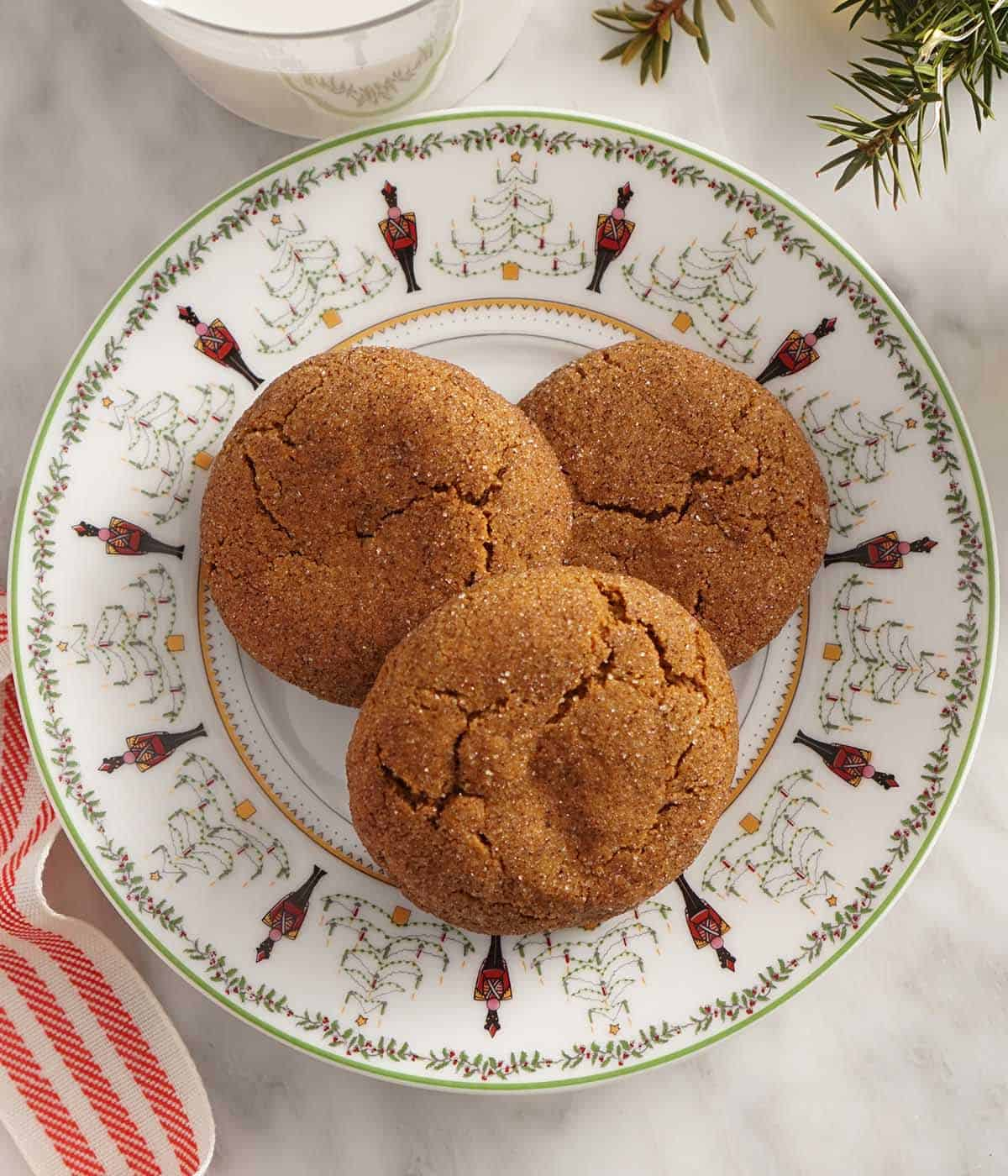 Gingersnap cookies on a holiday plate next to a glass of milk and a red ribbon.