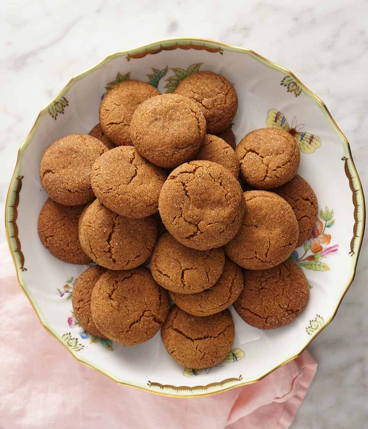 A porcelain bowl filled with gingersnap cookies.