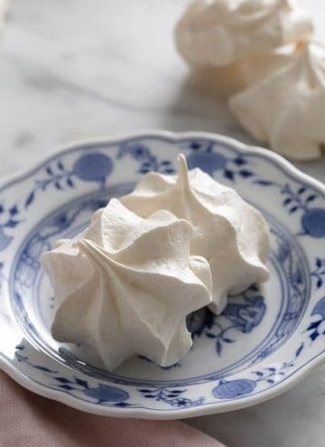 Two meringue cookies on a blue and white plate.