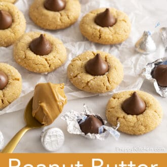 peanut butter blossoms scattered on a piece of white parchment paper
