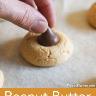 a chocolate kiss being placed onto the peanut butter cookie base