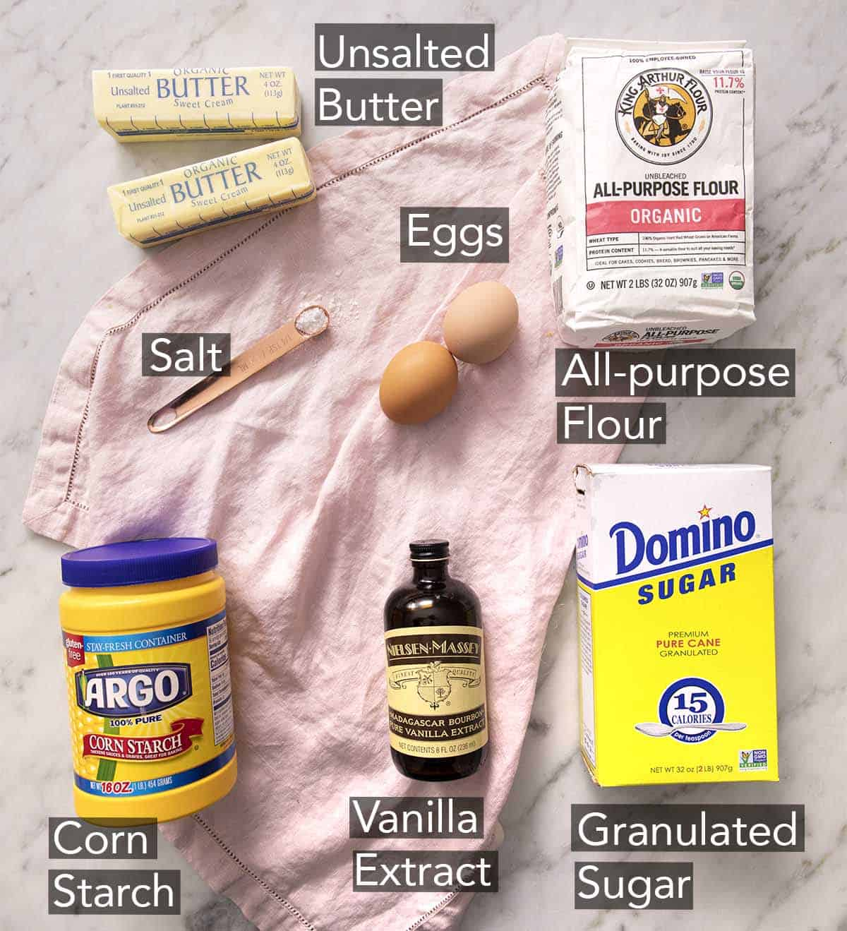 Ingredients to make sugar cookies laying on a marble counter.