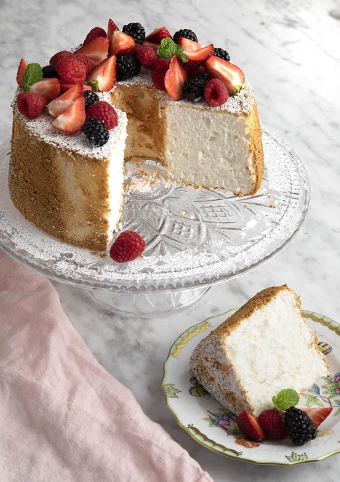 An angel food cake topped with fruit on a crystal cake plate.