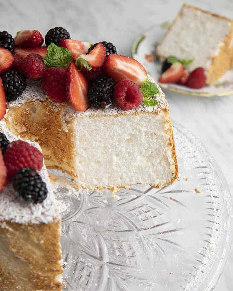 An angel food cake topped with fruit and with a slice removed.