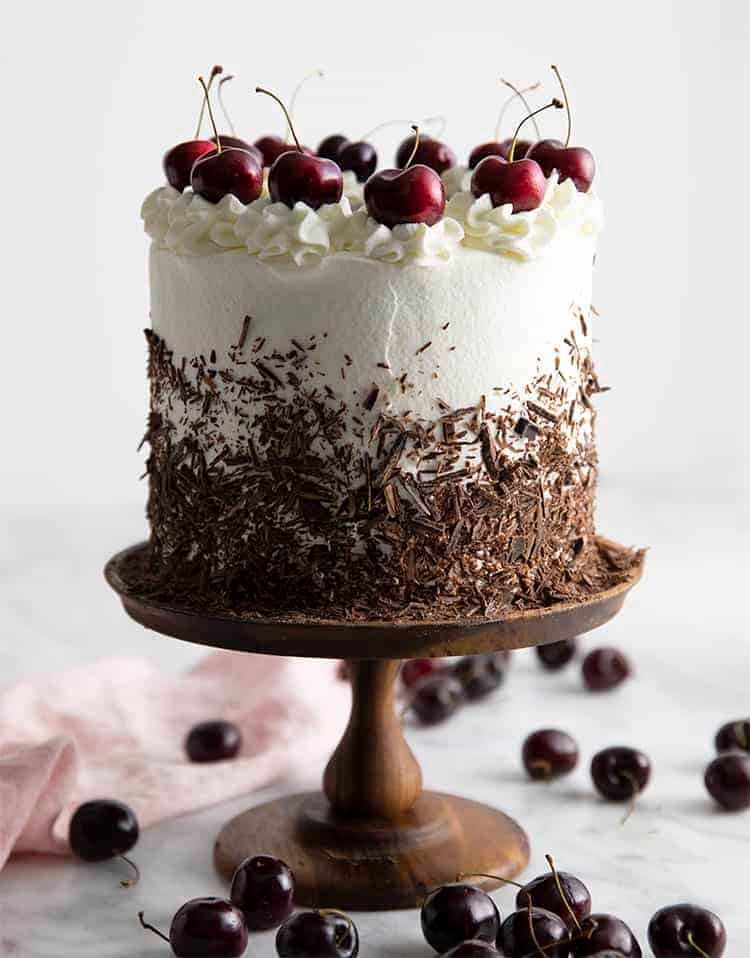 A black forest cake with chocolate shavings and cherries on top.