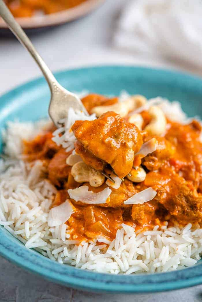 A fork picking up a bite of butter chicken from a bowl