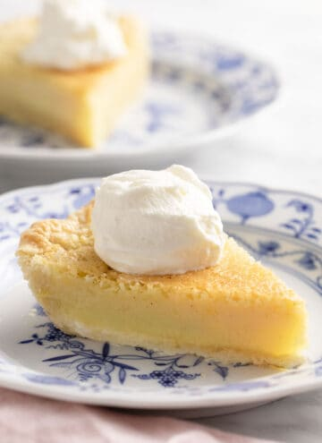Two pieces of buttermilk pie with whipped cream on a marble table.
