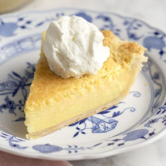 A piece of buttermilk pie on a blue and white plate.