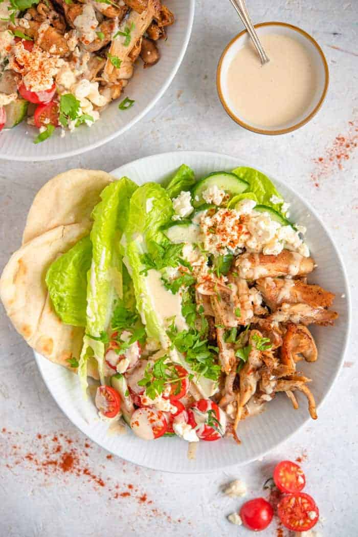 An overhead shot of chicken shawarma in a bowl with dressing, feta and salad
