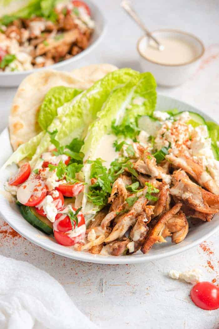 A side shot of chicken shawarma in a bowl with salad and dressing