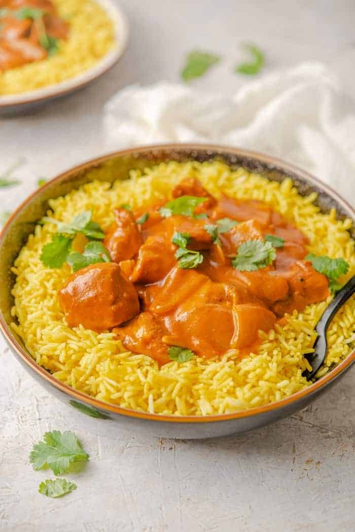 A side shot of Chicken Tikka Masala in a bowl with rice