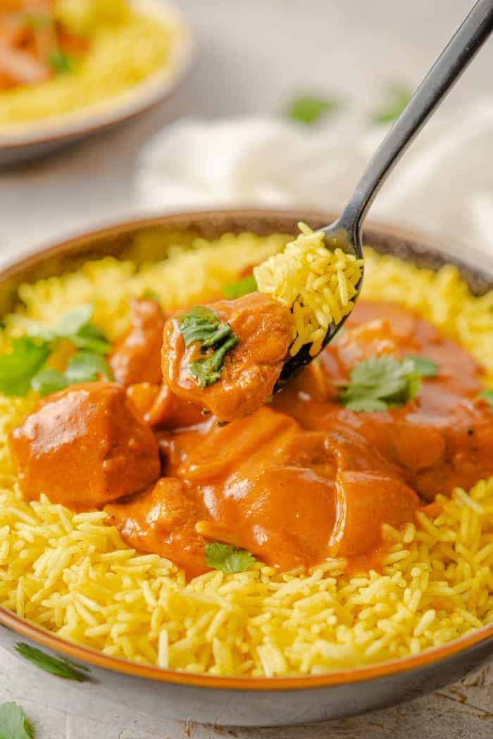 A close up of a fork picking up some chicken tikka masala from a bowl