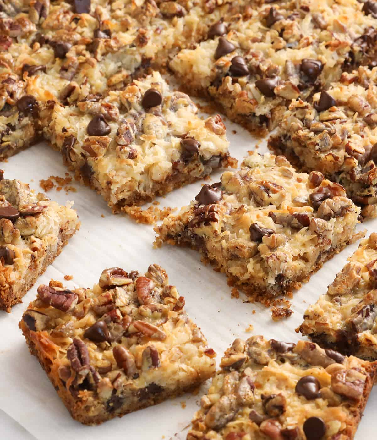 Magic cookie bars on a sheet of white parchment paper.