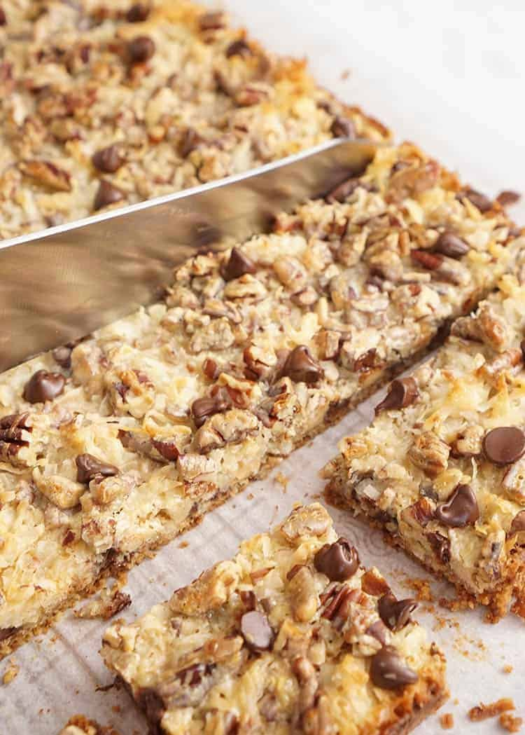 A block of magic cookie bars getting cut into squares.
