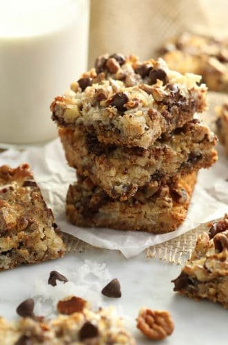 A stack of magic cookie bars next to a glass of milk.