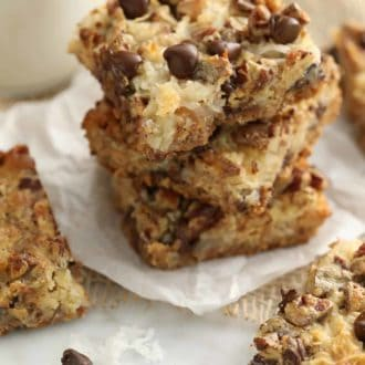 stacked magic cookie bars on parchment paper