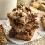 A stack of magic cookie bars with chocolate chips on top.