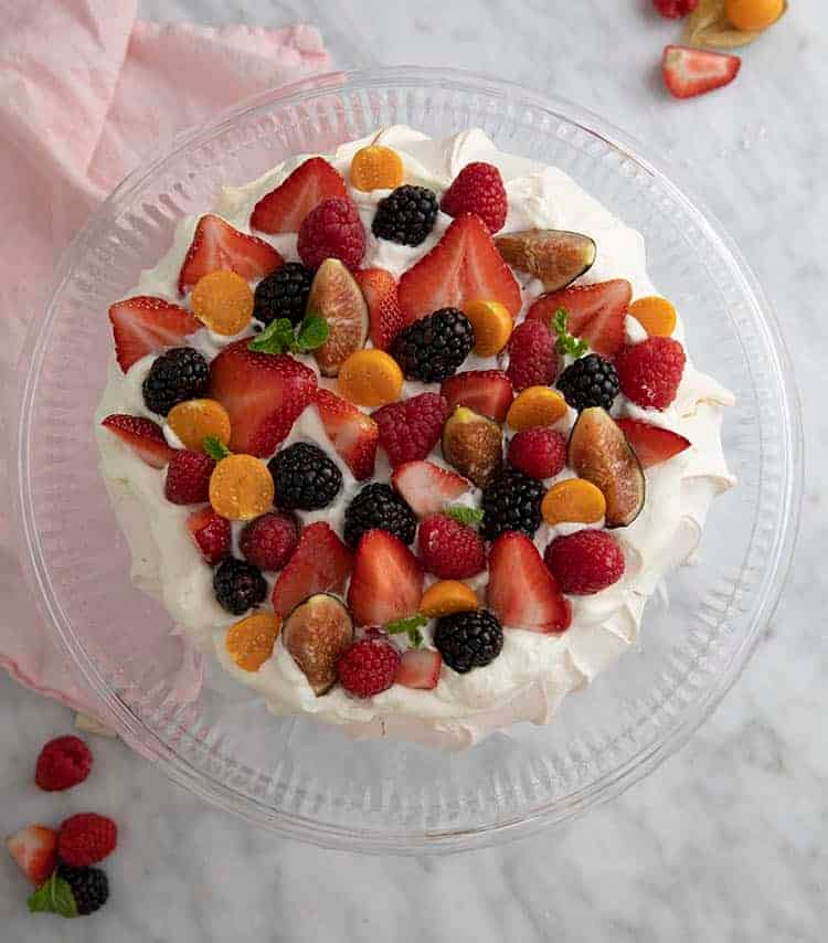 An overead shot of a pavlova topped with whipped cream and fruit