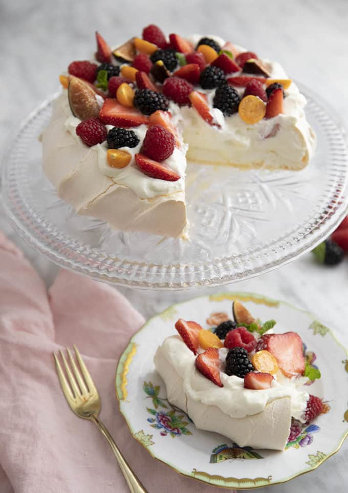A pavlova on a crystal cake stand with a piece cut out in the foreground.