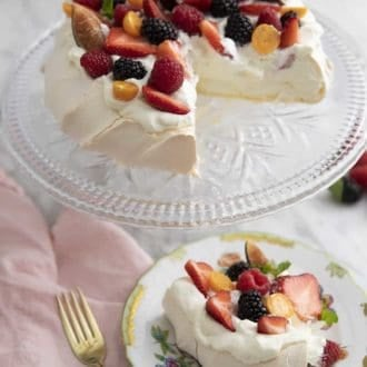 piece of pavlova topped with berries on a plate