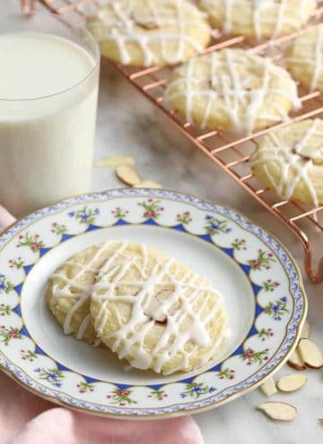 Almond cookies topped with two almond slivers and an almond glaze.