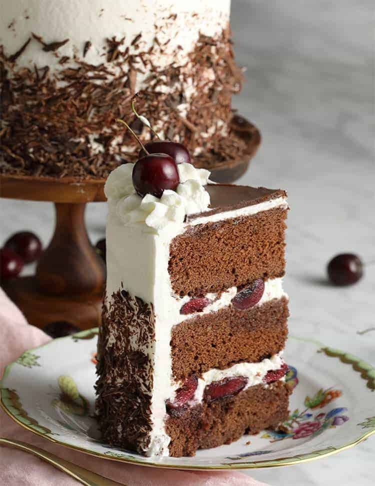 A piece of black forest cake topped with cherries on a porcelain plate.