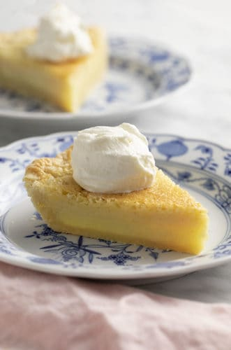 pieces of buttermilk pie with whipped cream on a marble table.