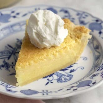 A piece of buttermilk pie topped with whipped cream on a blue and white plate.