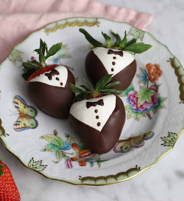 Strawberries covered with white and dark chocolate in the pattern of a tuxedo.