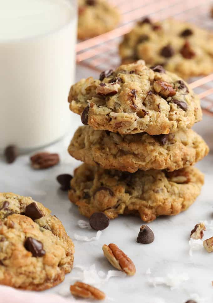 A stack of cowboy cookies next to a glass of milk.
